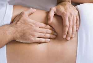 Picture of an osteopaths hands treating low back pain